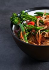 A Close Crop Image of Noodles and Vegtables in a tomato and Soy Sauce.